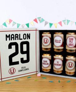 caja de 6 latas de cerveza pilsen con diseño del equipo de universitario